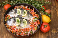 Sea fish. Raw sea fish with lemon, tomatoes, onion and rosemary. Before cooking. Mediterranean cuisine stock photos