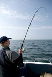 Sea fishing. A man standing in a motorboat, fishing at the sea or ocean. The fishing rod bent Stock Image
