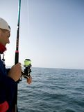 Sea fishing. A man standing in a motorboat, fishing at the sea or ocean. Seen from a side, copy space. SEA FISHING COLLECTION royalty free stock image