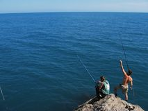 Sea fishing. Two guys fishing Royalty Free Stock Photography