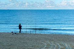 Sea fishing, fisherman on the shore and four fishing rods royalty free stock images