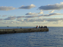 Sea fishing from the pier, Sochi resort, Russia. Fishermen with fishing rods on the pier, calm sea, evening clouds Stock Photos