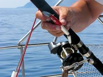 Sea fishing, spinning reel and fishing hook close-up. Sea fishing on yacht. Fisherman is holding spinning rod in tanned hand. Close-up spinning reel and fishing Stock Photography