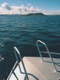 Sea fishing from steel fishing boat on open water. Rocky island et horizon. stock photos