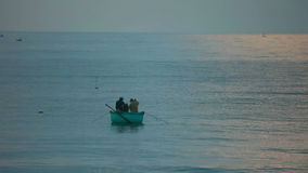 Sea fishing. Two fishers in round fishing boat at the sea stock video