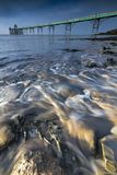 Incoming tide at Clevedon on Somerset coast. The sea flows up the beach on the North Somerset coast with Clevedon Victorian pier in the background Stock Photos