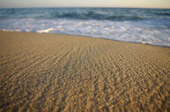 Sea foam. An ocean wave with the focus on the sand in front stock images