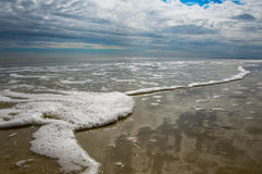 Sea Foam. Picture of a beach sea foam and a cloud filled sky Royalty Free Stock Image