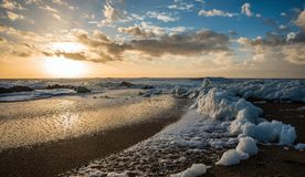 Sea foam on the beach at sunset Stock Photo
