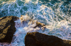 Sea foam from a cliff Stock Photos