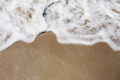 Sea foam with golden sand Stock Image