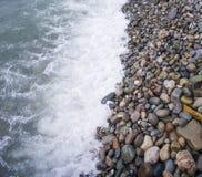 Sea foam on the pebble beach Seascape with tide Stock Photography
