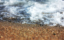 Sea foam on sand Stock Photo