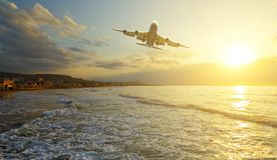 Passenger plane is taking off on the background of the sea shore at dawn and sunset royalty free stock photos