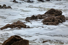 Sea foam and stones Royalty Free Stock Photography
