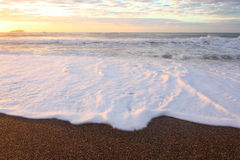 Sea spray at beach by sunrise Stock Photography