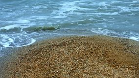 Sea foam on wave of water on background sandy shore on summer beachs. Sea foam on sandy shore at summer beach. Stormy sea waves with foam and splashes on sandy stock video