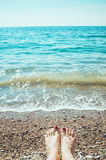 Sea foam, waves and naked woman feet on a sand beach. Girl legs relaxing. Vacation holidays, relax, summer background Royalty Free Stock Image