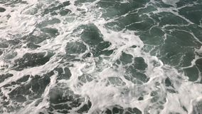 Sea with foam waves. Restless movement of foamy waves. Background of water in the sea. View from above stock footage