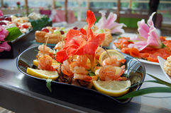 Sea food design. Table with mediterranean sea food made of shrimps, lemon, pine-apple, salmon, presented with flower decoration Stock Images