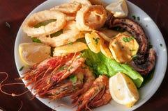 Sea food plate. Squid rings, grilled prawns, octopus, lemon, salat Stock Images