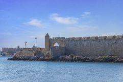 Sea in foreground and part of the castle and port at Greek island. Rhodes Royalty Free Stock Photo