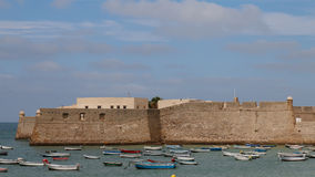 Sea Fort. Small boats shelter in the lee of an ancient defensive fortress in Cadiz, Spain Stock Photos
