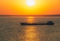Cargo ship sailing along the coast at dawn. Picturesque landscape. Royalty Free Stock Image
