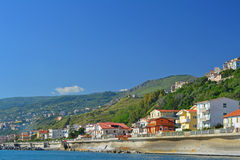 Sea front houses. A landscape photo of a coastal village with houses on the sea front and high in the hills above Stock Image