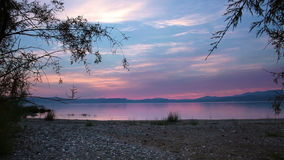 Sea of galilee through trees at sunset stock video footage