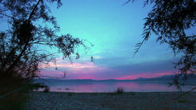 Sea of galilee through trees at sunset stock footage