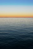 Sea gradient. Background with dark blue water and orange-azure sky gradient at twilight Stock Photo