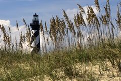 Seagrass framing the Hatteras Lighthouse. Sea grass placed in front of the Hatteras Lighthouse to give a perspective of distance and scale Stock Photo