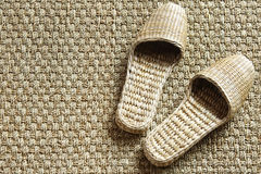 Sea-grass slippers on woven carpet Royalty Free Stock Photo