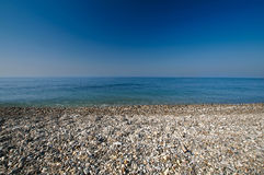 Sea gravel shore or beach and deep blue sky Royalty Free Stock Images