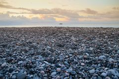 Sea gray pebbles on the seashore and yellow sunset. Sky stock image