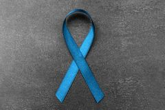 Sea-green ribbon on dark background. Ovarian cancer and gynecological disorders. Concept stock photo