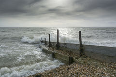 Sea groynes at Lee on the Solent UK. Sea in the Solent groynes at Lee on the Solent UK on a cloudy and breezy day with the sun trying to break through Royalty Free Stock Photo