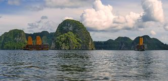 Sea gulf surrounded with high mountains and direct rocks. The ship floats in a sea gulf surrounded with high mountains and direct rocks in H Long Bay in Vietnam Stock Photography
