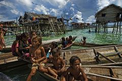 Sea Gypsies children in Sabah, Malaysia. Sea Gypsies children playing infront of their stilt houses in Sabah, Malaysia Royalty Free Stock Image