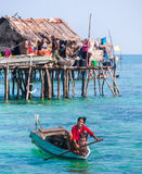 Sea Gypsy family on their sampan near their huts on stilts Stock Image