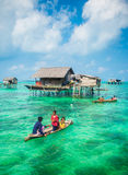 Sea Gypsy family on their sampan near their huts on stilts Royalty Free Stock Image