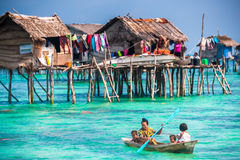 Sea Gypsy family on their sampan near their huts on stilts Stock Images