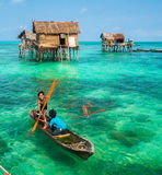 Sea Gypsy Kids on their sampan at their house on stilts Stock Images