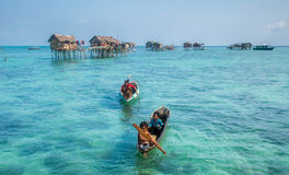 Sea Gypsy Kids on their sampan at their house on stilts Stock Photography