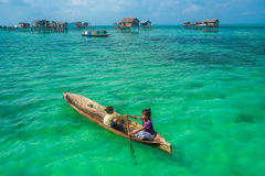Sea Gypsy Kids on their sampan with their house on stilts in the Stock Photography