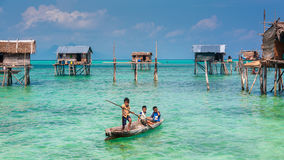 Sea Gypsy Kids on their sampan with their house on stilts in the Stock Images
