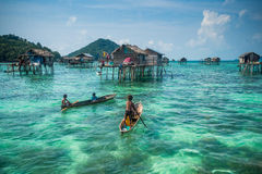 Sea Gypsy Kids on their sampan with their house on stilts in the stock image