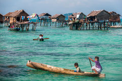 Sea Gypsy Kids on their sampan with their house on stilts in the Stock Photo