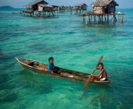 Sea Gypsy Kids on their sampan with their house on stilts in the Royalty Free Stock Photos